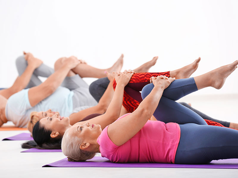 middle aged women doing yoga class